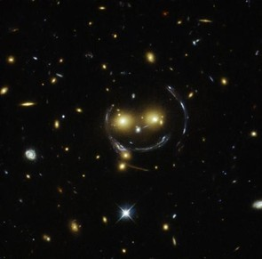 This smiling face is created by a group of galaxies being lensed by a massive galaxy. Credit: NASA/ESA/JPL-Caltech