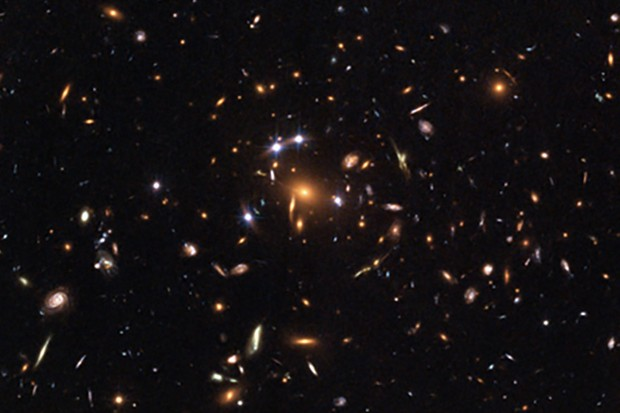 Credit: NASA, ESA, K. Sharon (Tel Aviv University) and E. Ofek (Caltech)  This Hubble image shows gravitational lensing in action as the light from a distant quasar is bent and multiplied by the gravity of a cluster of galaxies in front of it.