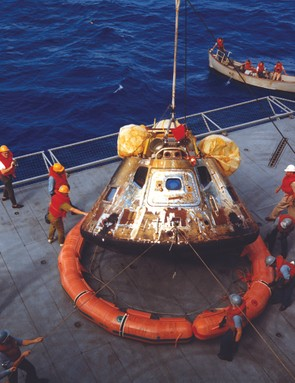 24 July 1969. The command module is lowered onto the deck of the USS Hornet to be prepared for transport back to the Lunar Receiving Laboratory in Houston. At the top are the three air sacks that inflated to right the module when it came to rest upside-down after splashdown. Credit: NASA