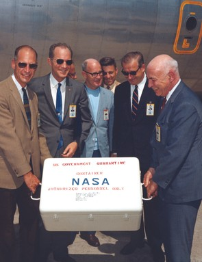 25 July 1969. NASA scientists are delighted to take charge of the first of Apollo 11's sample return containers full of lunar rocks, after it arrives by air at Ellington Air Force Base near Houston. Credit: NASA