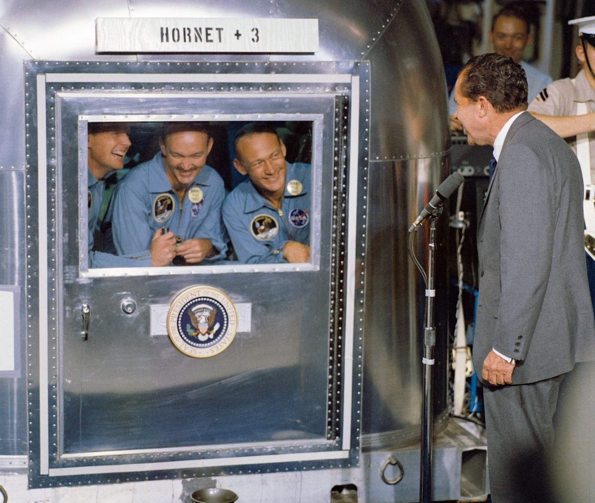 US President Richard Nixon welcomes the Apollo 11 astronauts back to Earth, aboard the USS Hornet. Here, Neil Armstrong, Michael Collins and Buzz Aldrin greet the President from the confines of their quarantine facility. Credit: NASA