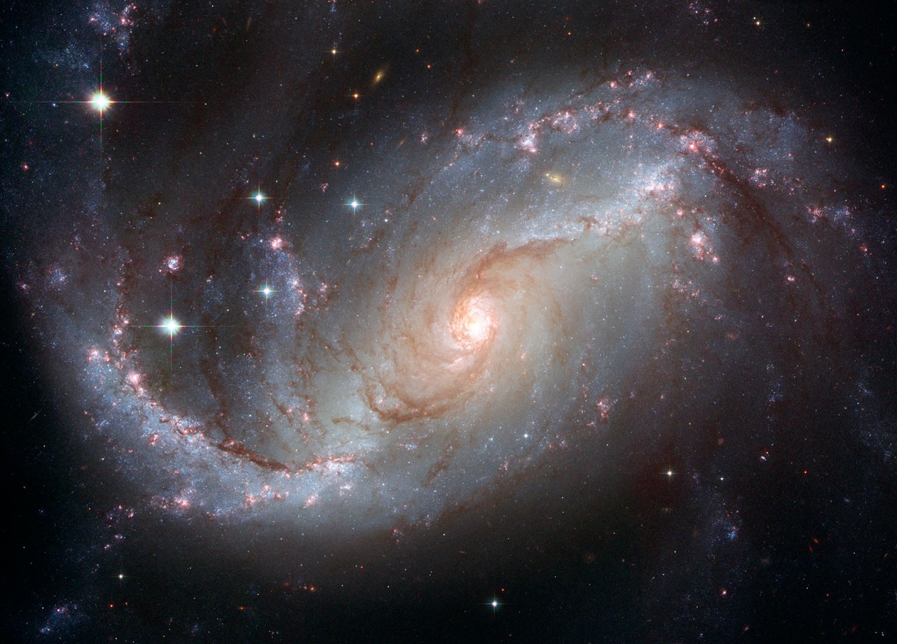 A Hubble Space Telescope image of spiral galaxy NGC 1672. Red and blue spiral arms draw the eye inwards towards the bright centre. Credit: NASA, ESA