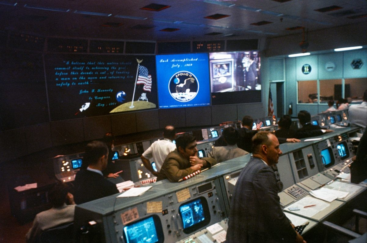 Mission Control during Apollo 11. On the monitors can be seen the mission patch, a quote by JFK and President Richard Nixon greeting the astronauts. Credit: NASA