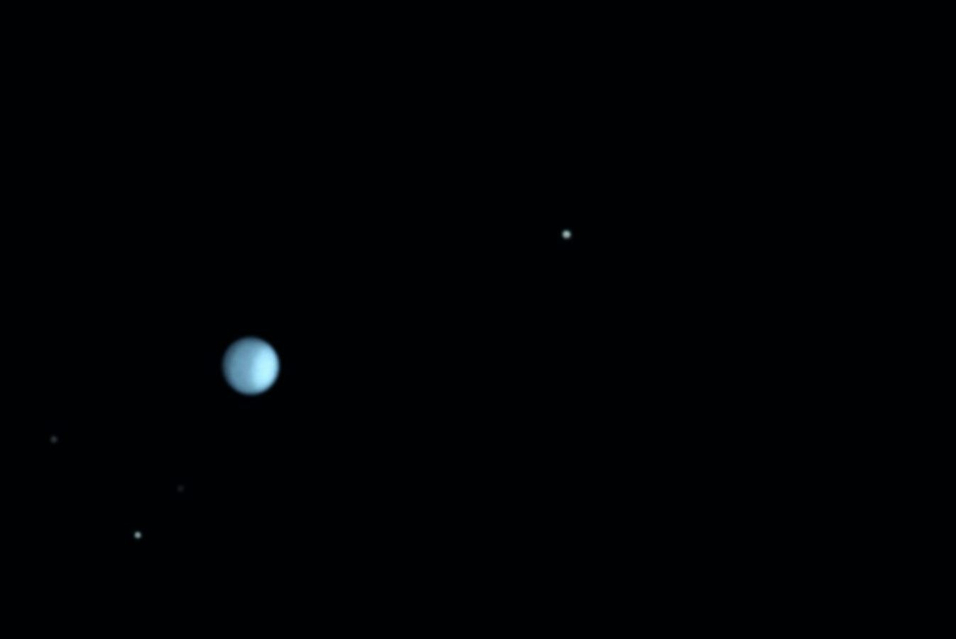 Uranus on 18 December 2017, showing surface details in infrared. The lighter polar region is tipped to the right. The moons were exposed separately from the planet and in visible light, not IR. Credit: Martin Lewis
