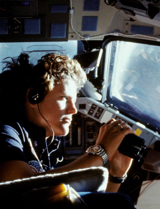 Kathryn Sullivan, the first American woman to spacewalk, uses binoculars to get a better view of Earth from the Space Shuttle cabin window, 6 October 1984. Credit: NASA