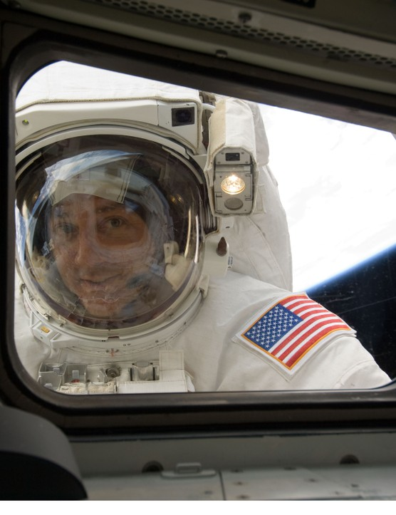 Astronaut Mike Massimino peers through the window of Atlantis during mission STS-125, May 2009. This was the last mission to service the Hubble Space Telescope. Credit: NASA