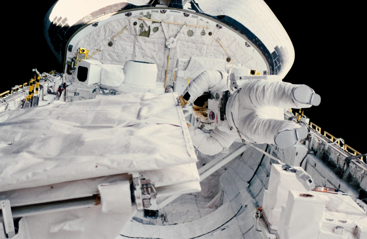 Kathy Sullivan becomes the first US woman to spacewalk, 11 October 1984. Here Sullivan is checking the latch of the SIR-B antenna in the Space Shuttle Challenger's open cargo. Credit: NASA