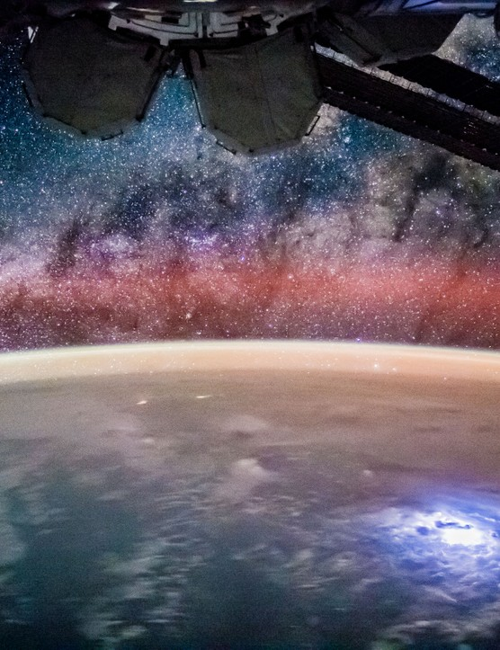 Aurora appears above Earth, photographed from the vantage point of the International Space Station.