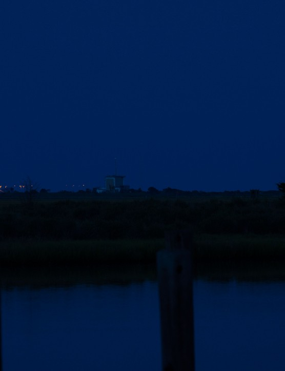 The full Moon seen to the right of the Orbital Sciences Corporation Antares rocket, with the Cygnus spacecraft onboard, Saturday, July 12, 2014, launch Pad-0A, NASA's Wallops Flight Facility in Virginia.