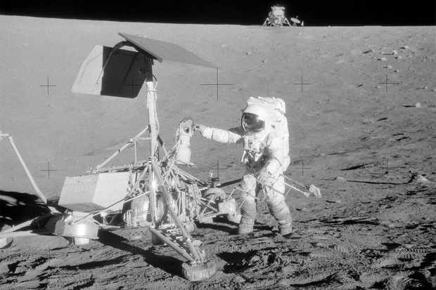 Pete Conrad next to the Surveyor 3 lander, with the lunar module on the crater rim just 182m away. Credit: NASA