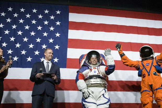 Spacesuit engineer Amy Ross (left) and NASA Administrator Jim Bridenstine (second from left) watch spacesuit engineer Kristine Davis wearing a prototype of NASA's Exploration Extravehicular Mobility Unit (xEMU), 15 October 2019 at NASA headquarters in Washington. Dustin Gohmert (right), Orion Crew Survival Systems Project Manager, sports the Orion Crew Survival System suit, Credit: (NASA/Joel Kowsky).