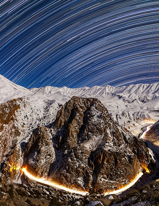 Long exposure image of star trails in a moonlit night of Alborz Mounatins, above a road passing through tunnels. Credit: Babak Tafreshi, TWAN