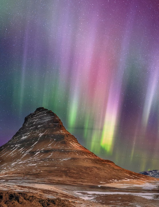 Strong and colorful appearance of aurora borealis, the northern lights, above Iceland. In the foreground is the iconic landmark of western Iceland, Kirkjufell (Church mountain) in Snæfellsnes peninsula. Credit: Babak Tafreshi, TWAN