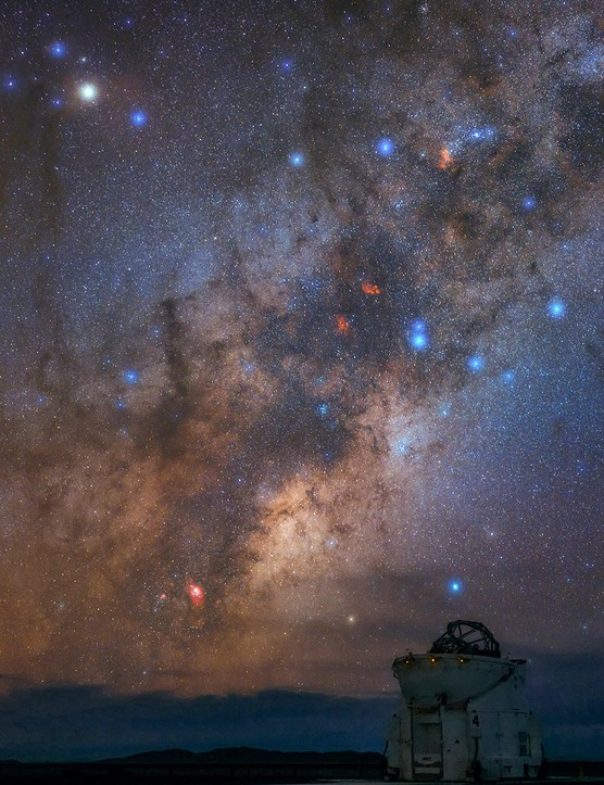The Milky Way in the constellations Scorpius and Sagittarius above the Cerro Paranal Observatory in the Atacama Desert, Chile. The Lagoon Nebula (M8) is the red cloud near the horizon, next to the Large Sagittarius Star Cloud (the brighter region of the Milky Way). The cloud is almost pointed toward the galactic center. Higher up in the sky are M6 and M7 star clusters at the tail of Scorpion. Two red emission nebulae at that area (image middle) are NGC 6334 or the Cat's Paw Nebula and NGC 6357 also known as the War and Peace Nebula. At 2,635 metres (8,645 ft) from sea level, with its dark and transparent sky, Paranal is home to the Very Large Telescope (VLT), operated by the European Southern Observatory (ESO). It is composed of four 8-metre telescopes and several 1-meter auxiliary telescopes (pictured here) which are important part of the VLT interferometer. Credit: Babak Tafreshi, TWAN