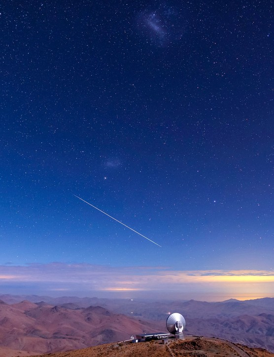A bright meteor streaks the sky next to the Large and Small Magellanic Clouds above a radio telescope and light of La Serena in a moonlit night of La Silla observatory, Chile. Credit: Babak Tafreshi, TWAN
