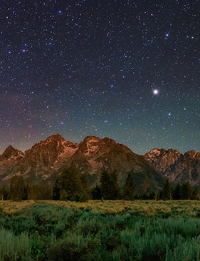 The night sky over the Grand Teton National Park in Wyoming, USA. The bright summer Milky Way appears on the left in Scorpius and Sagittarius, over the light of the nearby town Jackson Hole (towards south). In the middle is the bright star Arcturus and on the right is the Big Dipper (the prominent figure in Ursa Major) towards the north. The green bands are airglow; natural emission of the Earth upper atmosphere. The Teton Range is a part of the Rocky Mountains. The Grand Teton, the tallest mountain in the range, is 13,775 feet (4,199 m) high. Credit: Babak Tafreshi, TWAN