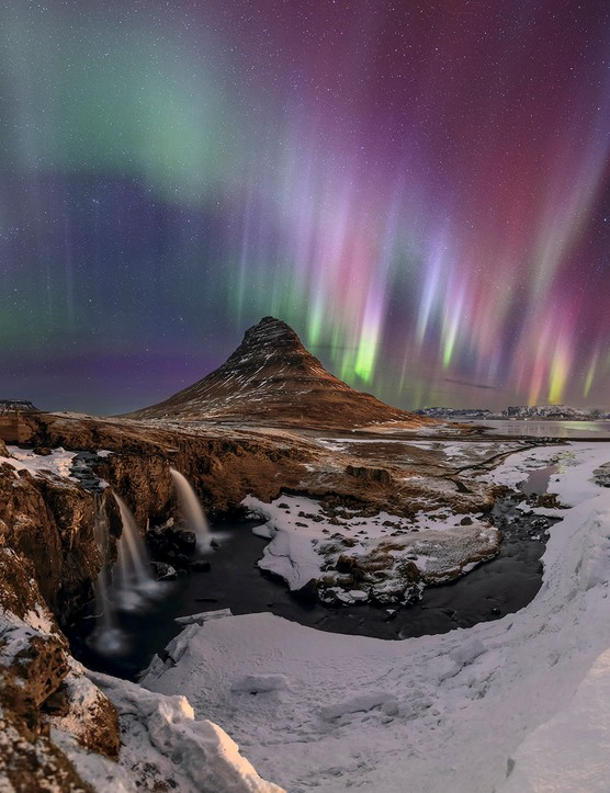 Strong and colorful appearance of aurora borealis, the northern lights, above Iceland. In the foreground is the waterfalls and mountain of Kirkjufell (Church mountain) in Snæfellsnes peninsula. Credit: Babak Tafreshi, TWAN