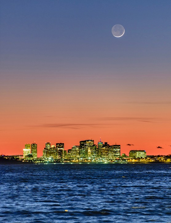 The New Moon in a colorful dusk above Boston skyline and the Atlantic Ocean. Credit: Babak Tafreshi, TWAN