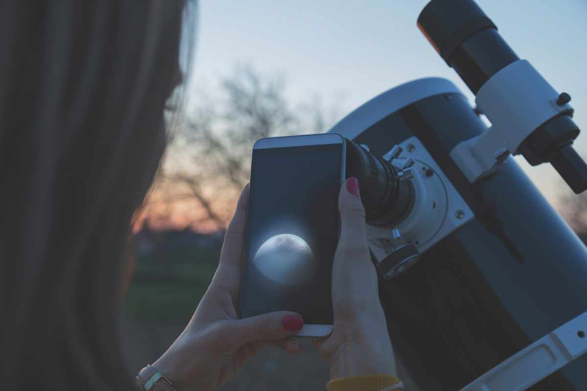 Photographing the Moon through a telescope with a smartphone. Credit: m-gucci / Getty Images