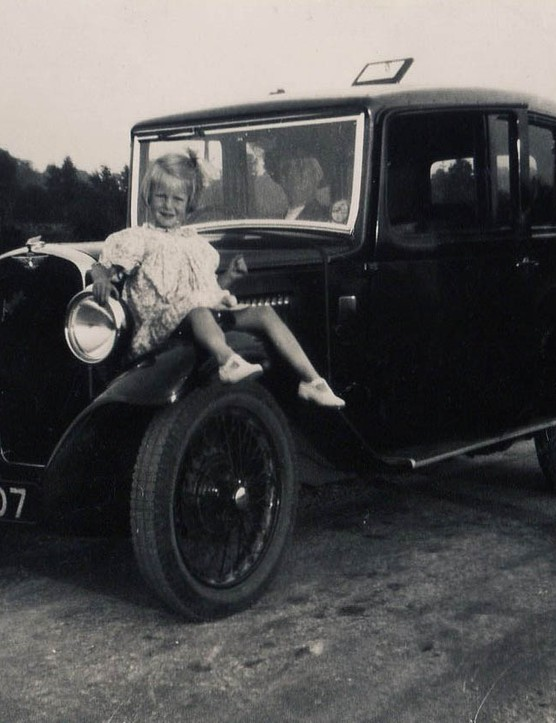 Young Jean Mundy sitting on a car