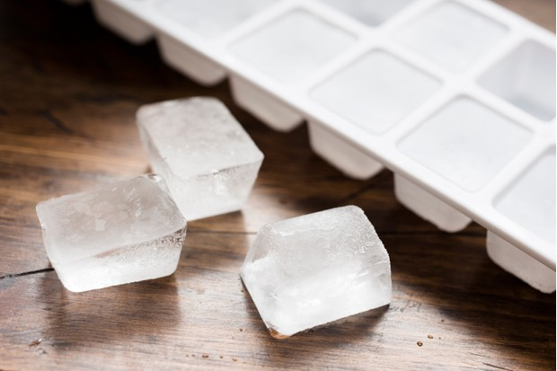 Ice cube tray filled with ice cubes and three lose ice cubes against dark wood.