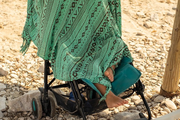 pram covered with blanket on a beach