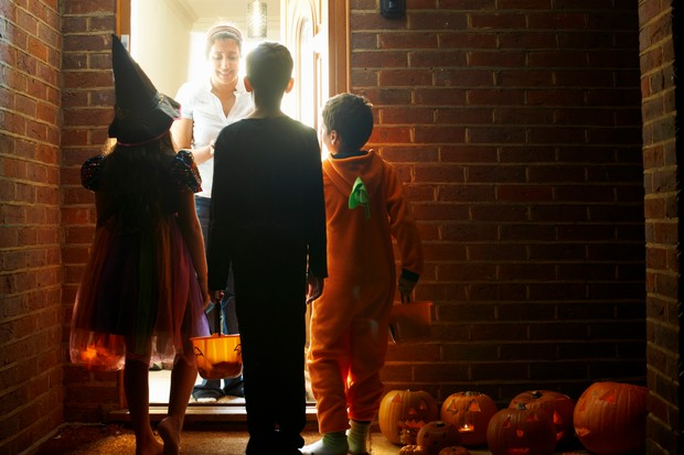 Rear view of three children wearing halloween costumes trick or treating