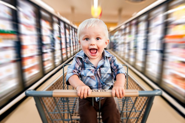 A baby boy in a shopping cart, speeding through a grocery parking lot.