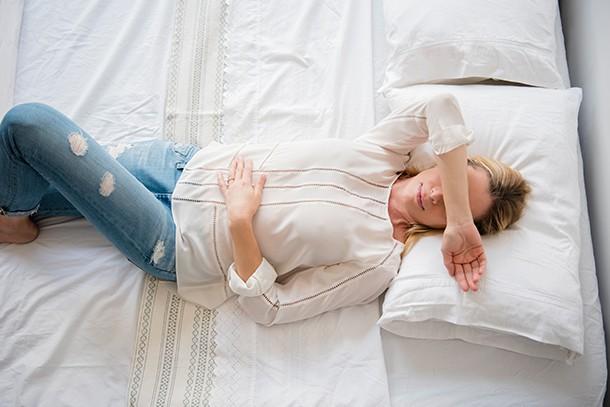 woman lying down sore eyes