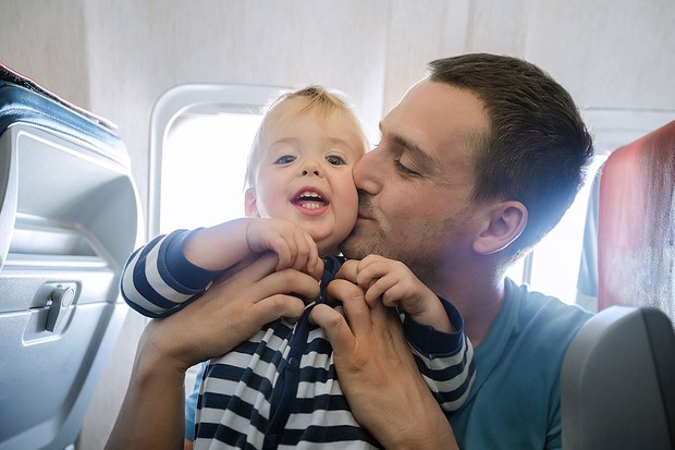 baby on a plane being kissed by his dad
