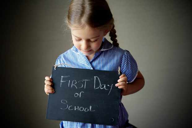 "Four year old girl with plaits and blue check dress holds a handwritten chalkboard sign that says, ""First Day of School""."