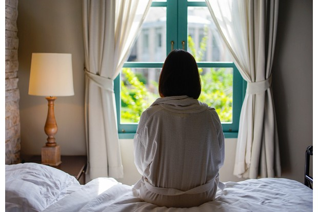 Lone woman sitting on the bed looking out at the window in the morning