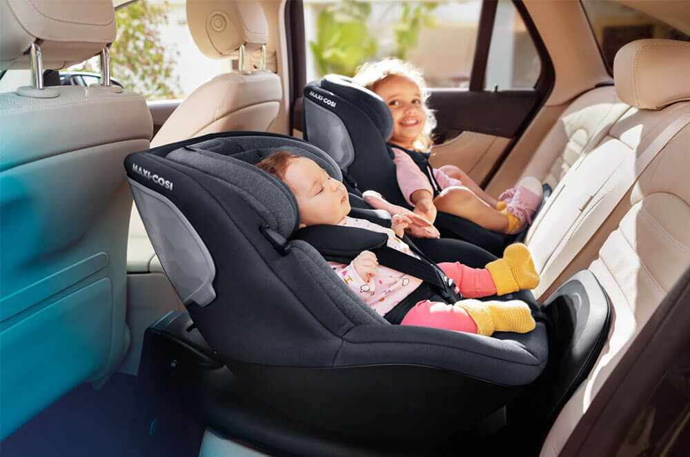 """Two children sitting in Mica car seats"""""""