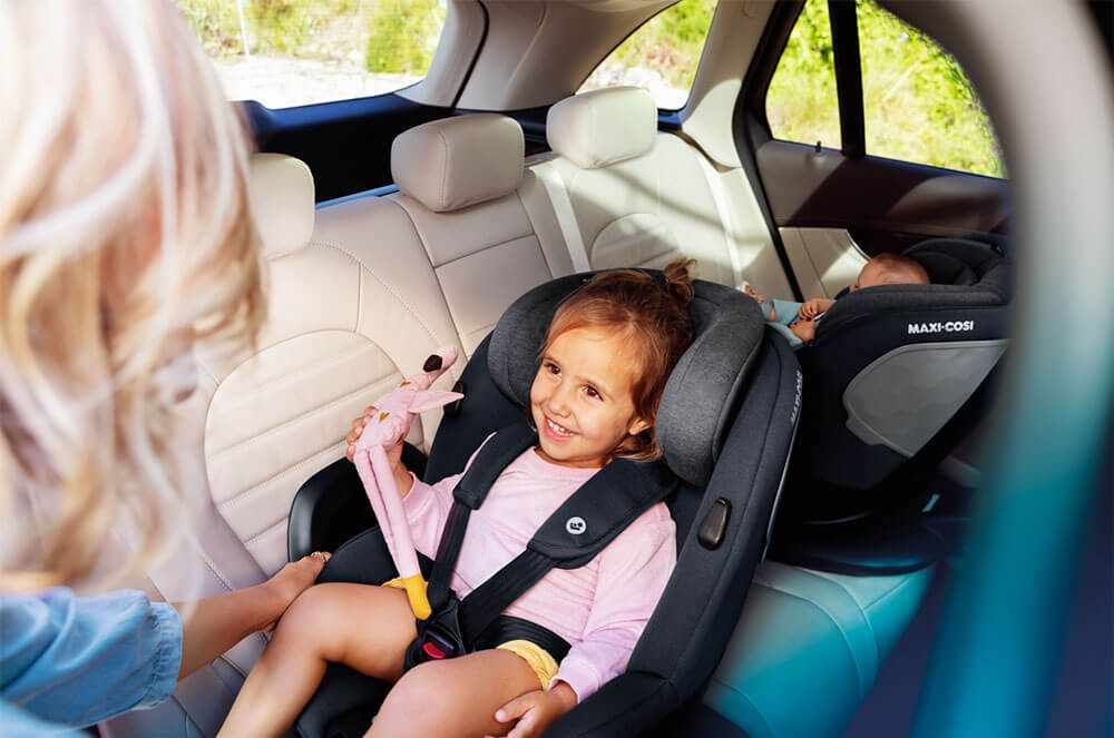 Mother looking at her two children in Maxi-Cosi car seats