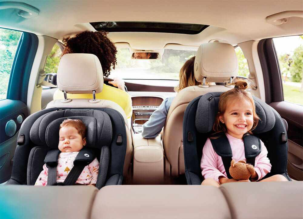 Two children sitting in the Maxi-cosi Mica car seats in the back of a family car with their parents in the front