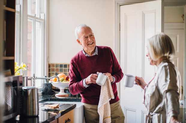 Senior man is talking to his wife in the kitchen. He is drying dishes and the woman is dirnking tea.