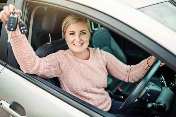 Portrait of a happy young woman holding the keys to a new car