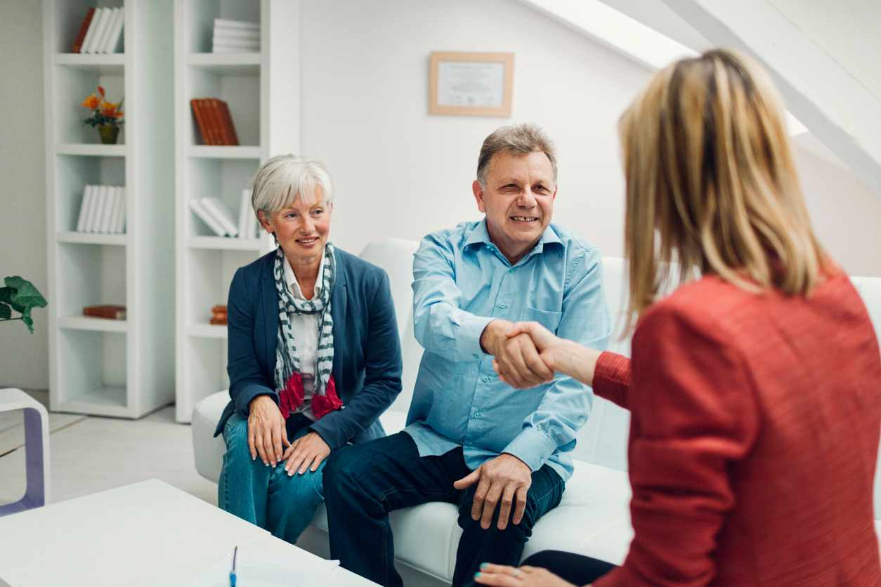 Mature couple meeting with financial advisor and talking about insurance and retirement options. Financial advisor handshaking with senior man after successful meeting.