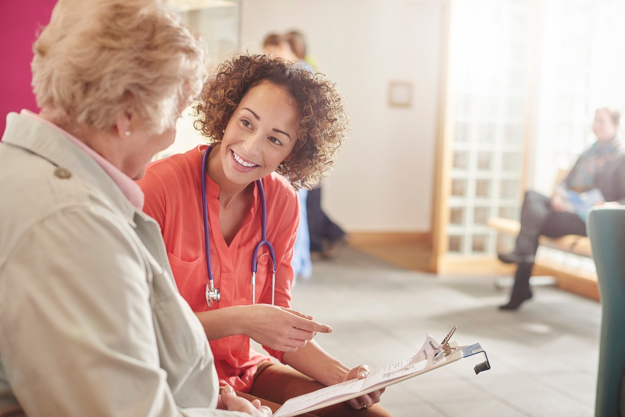 a  female doctor stands next to a senior patient in her waiting room and casually chats to her about her details . In the background a nurse chats to woman with her digital tablet , and a male patient stands at the reception desk and booking an appointment .