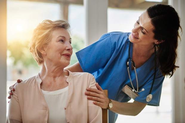 Shot of a smiling senior woman talking with a nurse in assisted living facility
