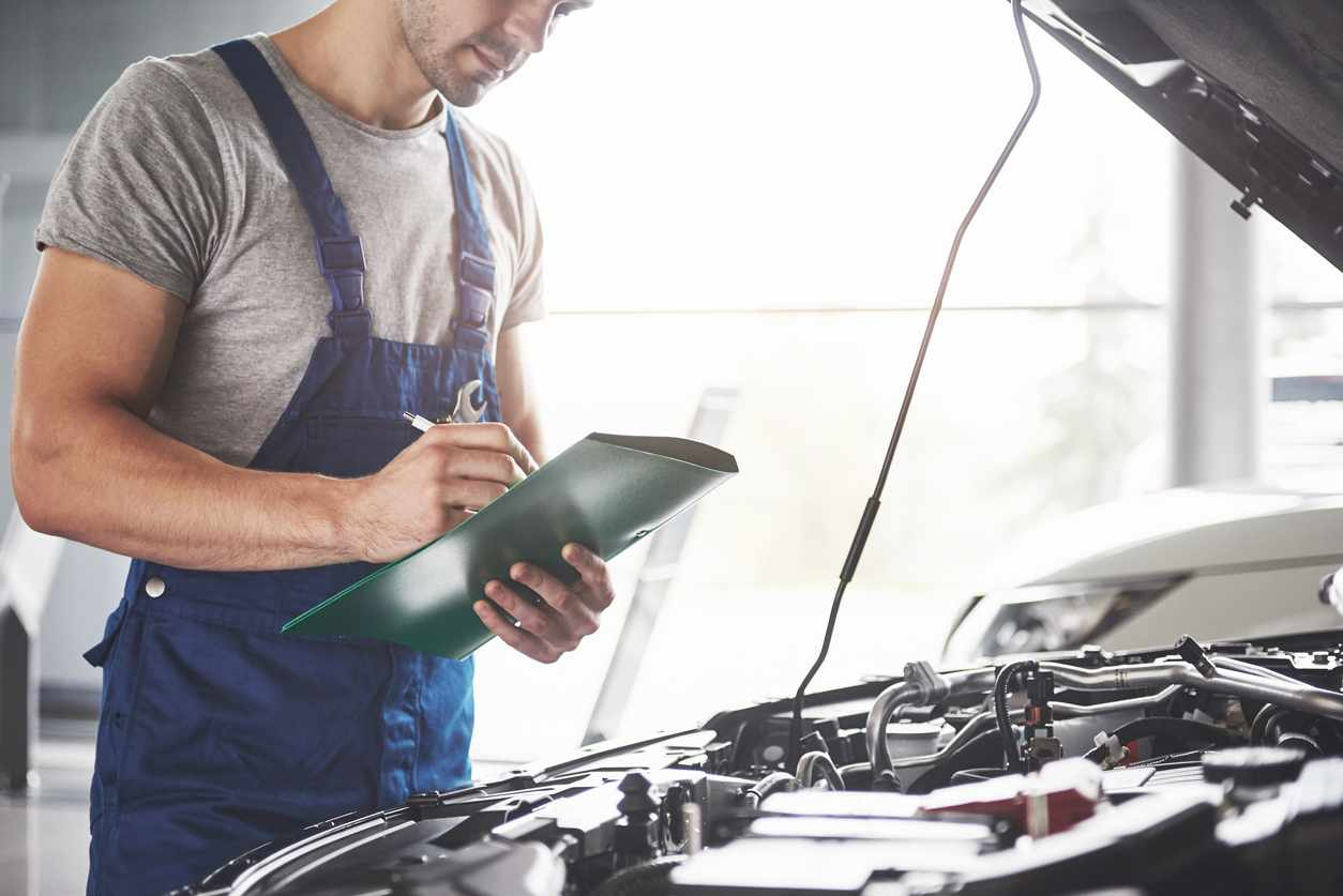 Portrait of a mechanic at work in his garage - car service, repair, maintenance and people concept.
