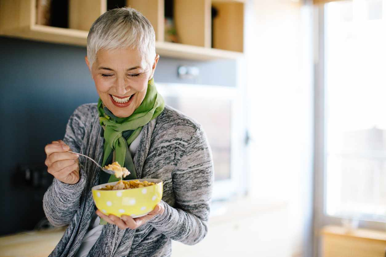 Mature woman having healthy beakfast. Shallow DOF. Developed from RAW; retouched with special care and attention; Small amount of grain added for best final impression. 16 bit Adobe RGB color profile.