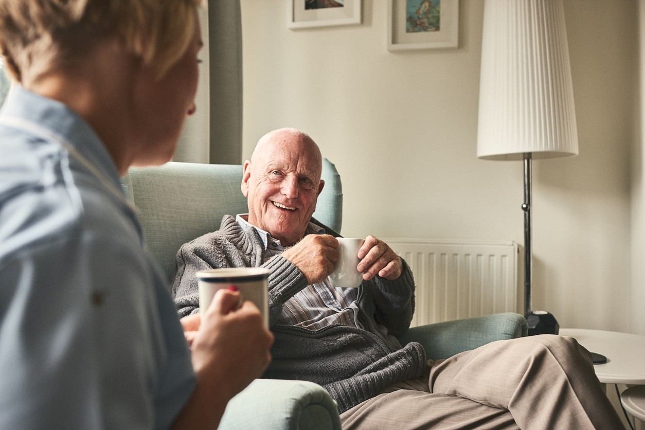 Smiling senior man with cup of coffee talking to female caregiver sitting in front at care home