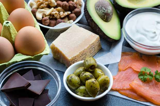 This is a table top shot of food items high in healthy fats. Eating healthy fats can help with weight loss and are the cornerstone of a high-fat low-carb diet (Ketogenic or Keto diet). These include: smoked salmon, dark chocolate, eggs, parmesan cheese, mixed nuts (almonds, walnuts, hazelnuts and cashews), full-fat yogurt (Greek yogurt), green olives with herbs and two avocado halves. Not only are these foods high in fat, they are also high in vitamins and minerals which support a healthy lifestyle.