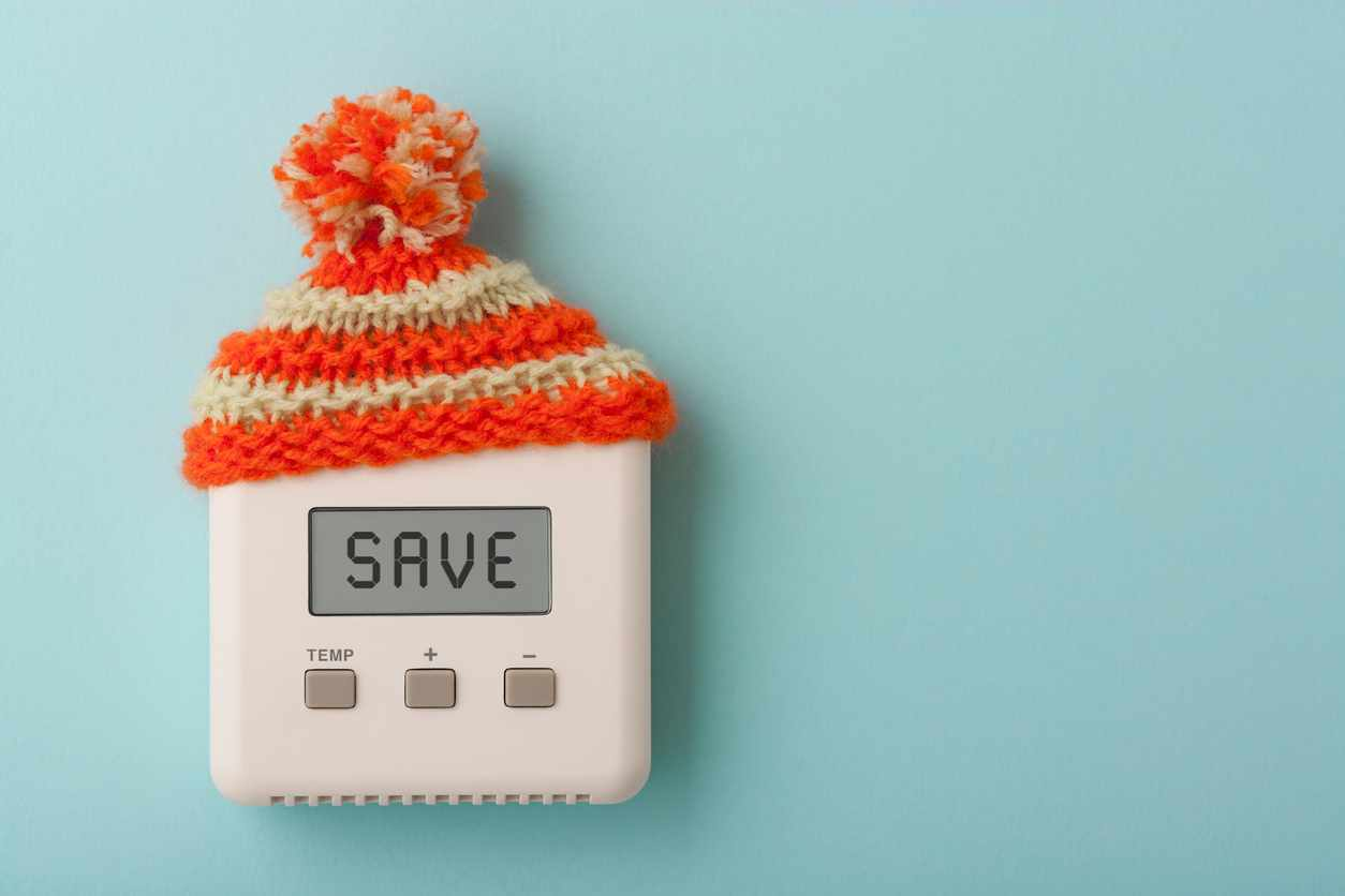 The word SAVE on a digital room thermostat wearing wooly hat.