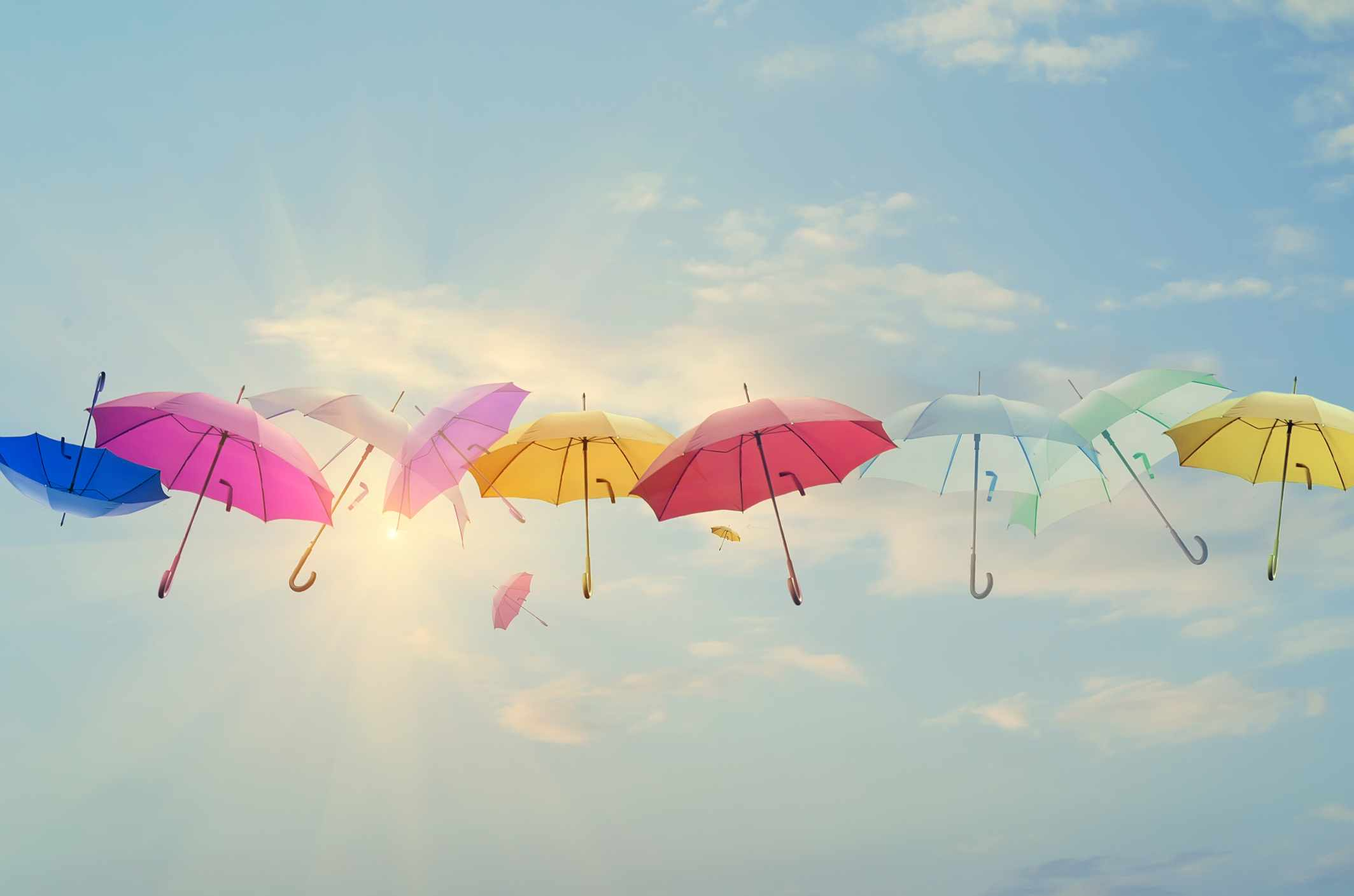 Conceptual photo of different color umbrellas lined-up across the sky. Sun is behind them shining, and this concept can represent team work, individuality, success of different people working together etc.
