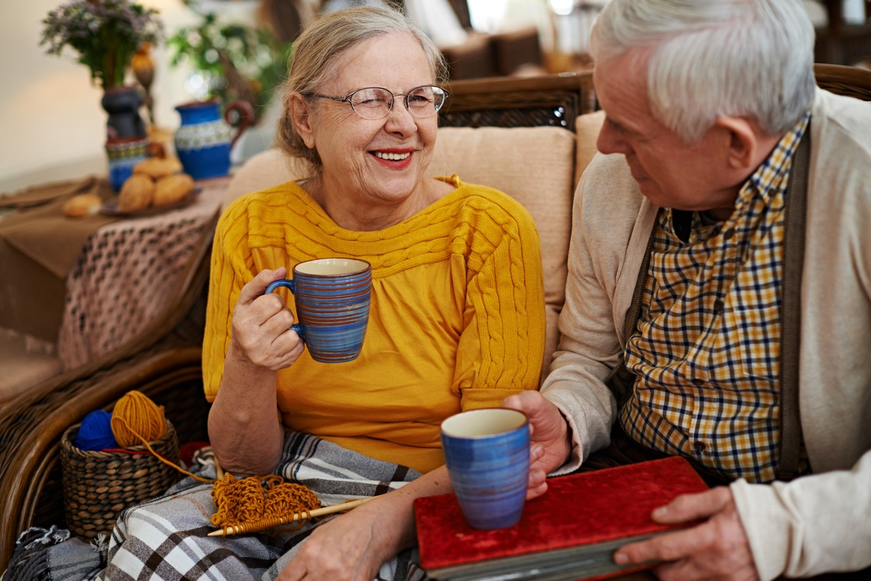 Seniors drinking tea and laughing at home