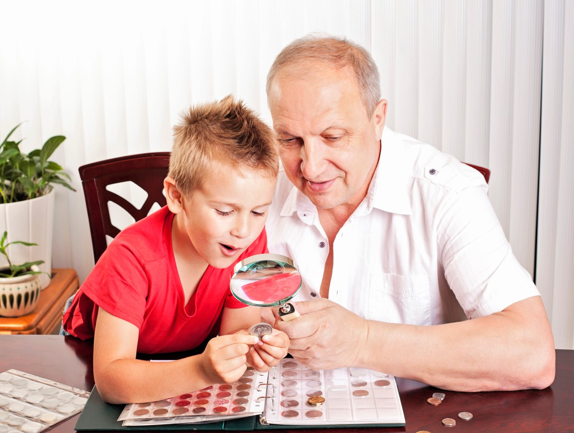 Grandfather showing his coin collection to his excited grandson