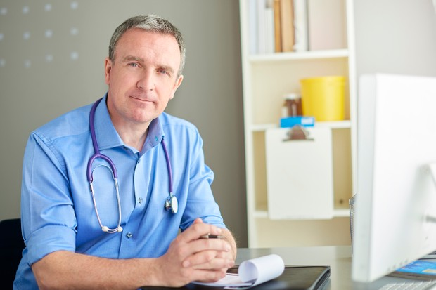 male gp sits at his desk and smiles to camera
