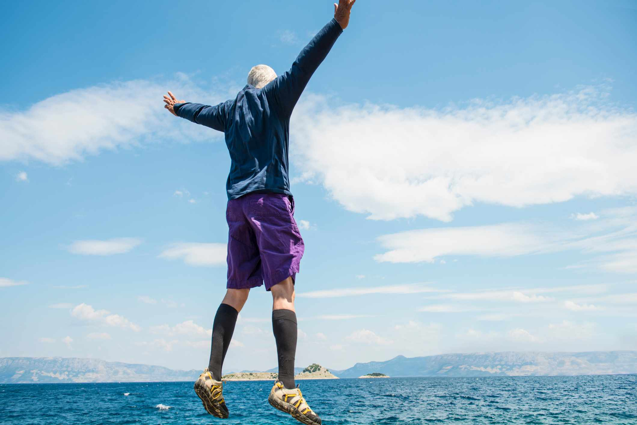 Low angle view of senior men jumping up with arms raised against blue sea and blue sky on sunny summer day. He wears shorts and t-shirt. Rear view.